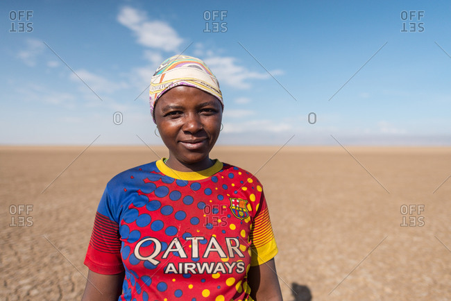Tanzania, East Africa - November, 2016: Content African woman in casual t shirt and headwear smiling and looking at camera with blue sky and empty desert on background in Tanzania