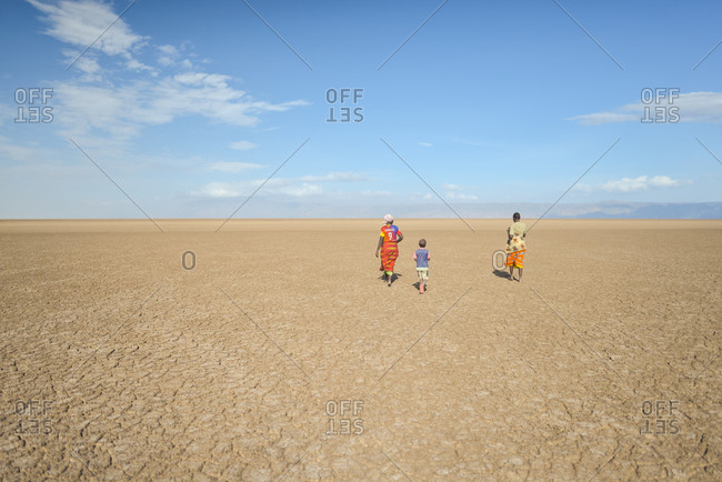 Tanzania, East Africa - November, 2016: Back view of faceless local citizens in casual wear walking in empty desert with blue sky on background in Tanzania