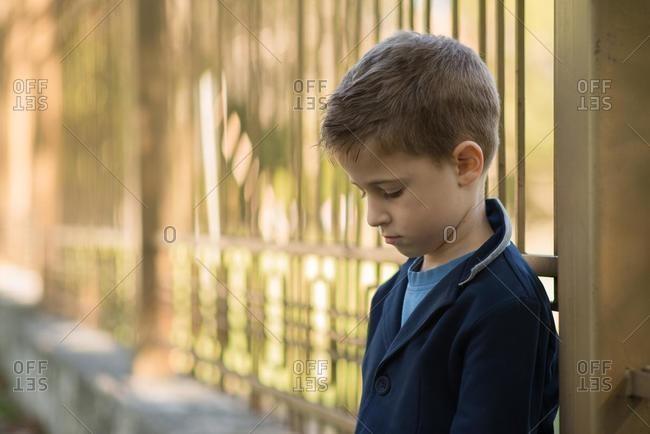 Portrait of a sad boy leaning against metal railings