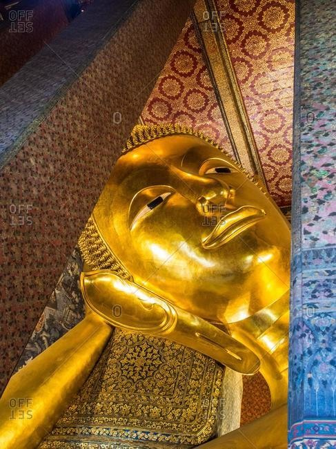 Portrait of a golden reclining Buddha in a temple, Bangkok, Thailand