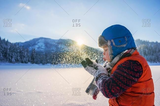 Portrait of a Boy blowing a handful of snow, USA