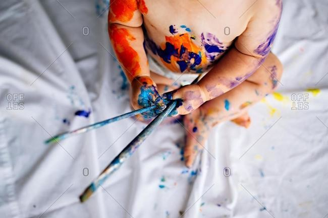Baby boy covered in paint holding paint brushes