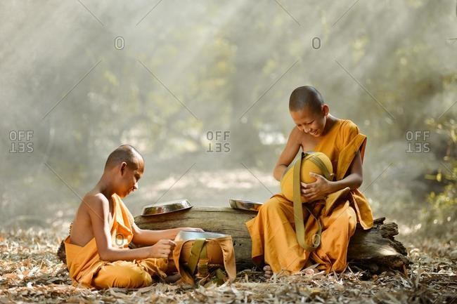 Two novice Buddhist Monks sitting in forest cleaning food bowls, Thailand
