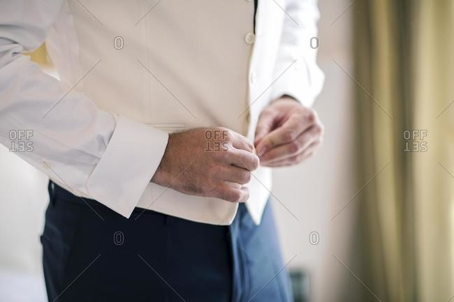 Close-up of a man buttoning his waistcoat