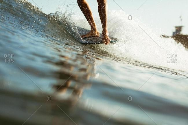 Close-up of a woman surfing a wave, Malibu, California, USA