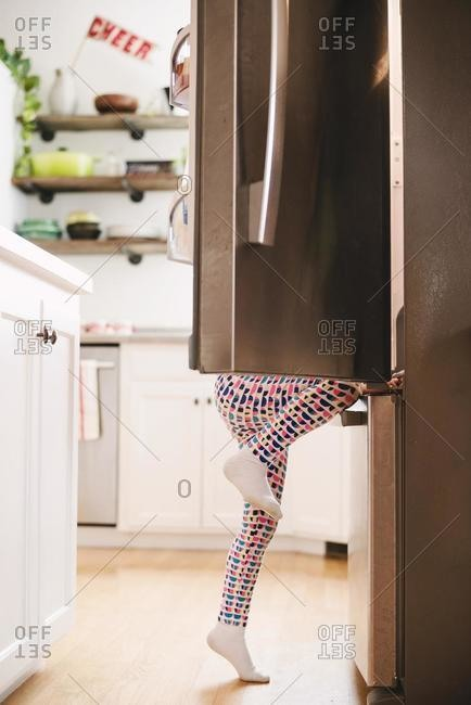 Young girl climbing into a refrigerator