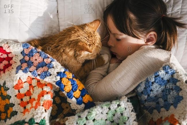 Girl having a nap with her cat