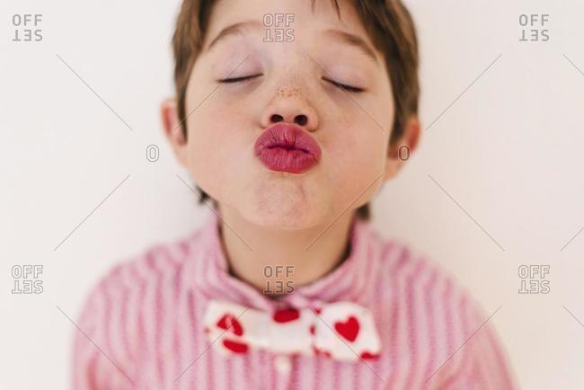 Portrait of a boy blowing a kiss