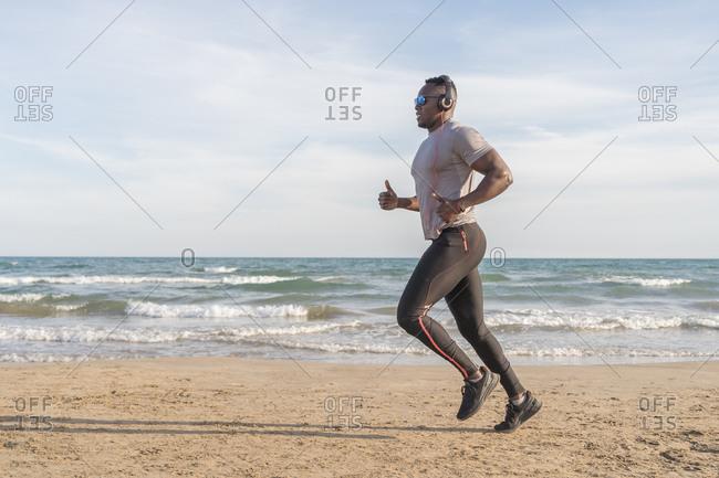 Black man running on the beach in Barcelona, Spain