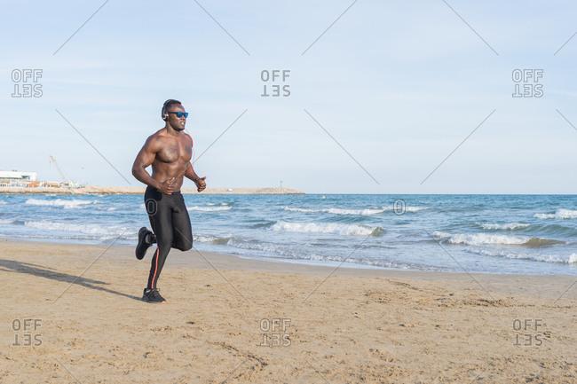 Muscular black man running on the beach in Barcelona, Spain