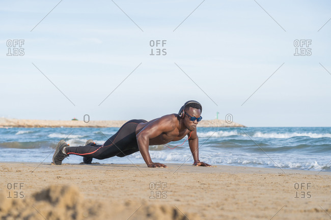 Muscular black man doing push-ups on the beach in Barcelona, Spain