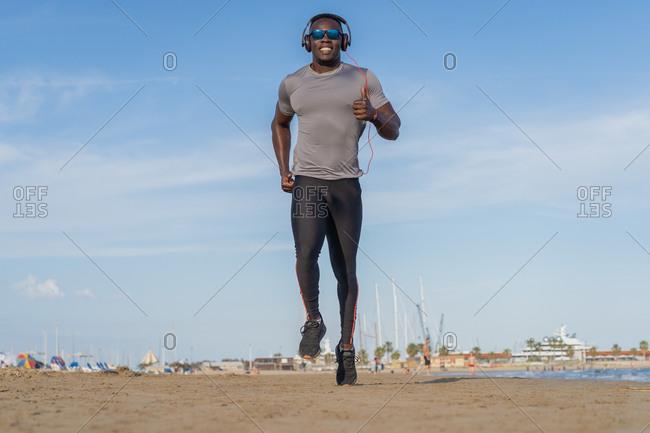 Muscular black man running on the beach in Barcelona, Spain.