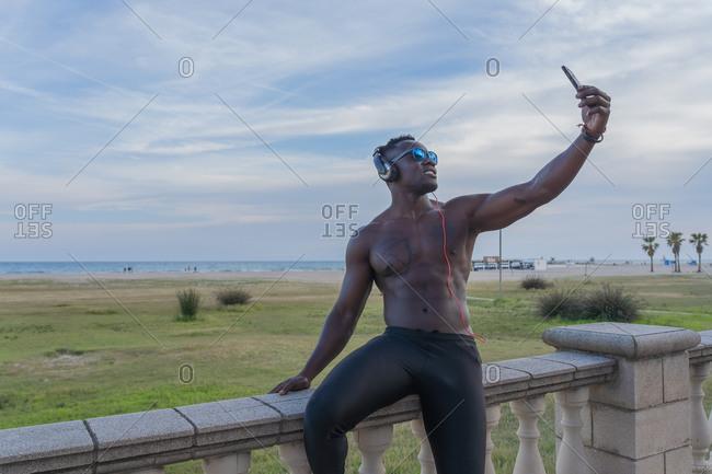 Muscular sportsman taking a selfie on the promenade