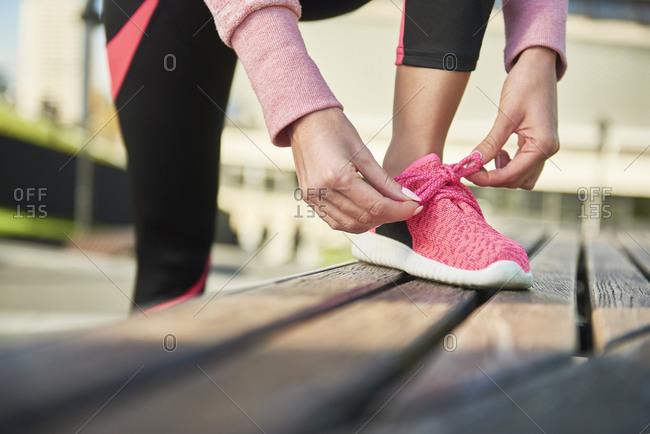 Legs of female runner- tying shoelaces