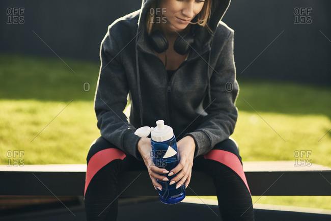 Woman taking a break after workout- holding drinking bottle