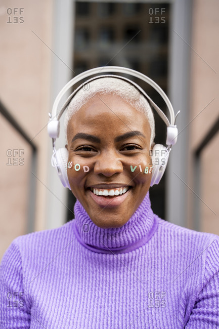 Portrait of white haired woman with white headphones and stickers in her face- good vibes