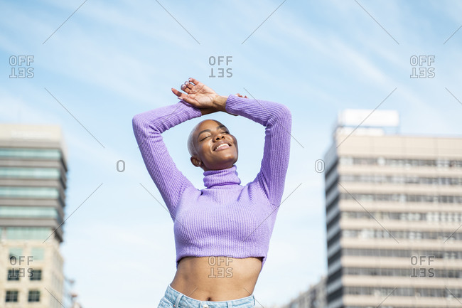 Portrait of white haired woman with closed eyes and raised arms