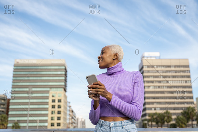 Portrait of white haired woman with smartphone in the city