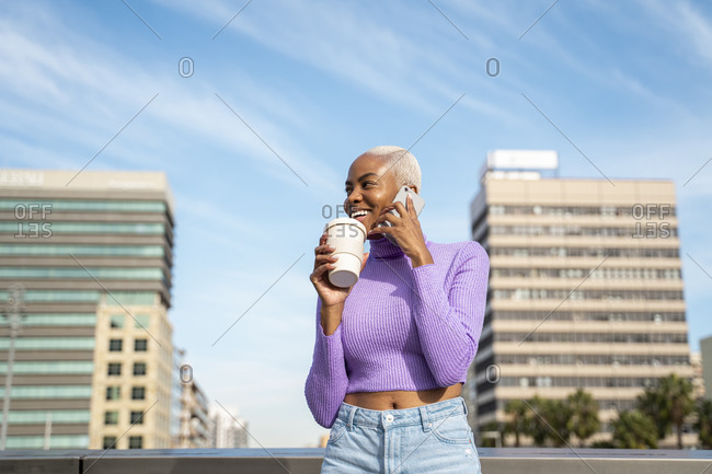 Portrait of white haired woman using smartphone and coffee to go