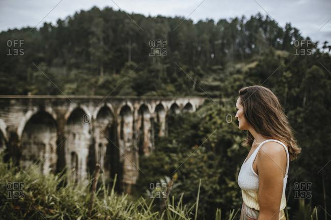 Sri Lanka- Uva Province- Demodara- Adult woman admiring view of Nine Arch Bridge