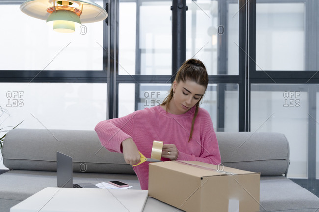Young woman sitting on couch packing parcel