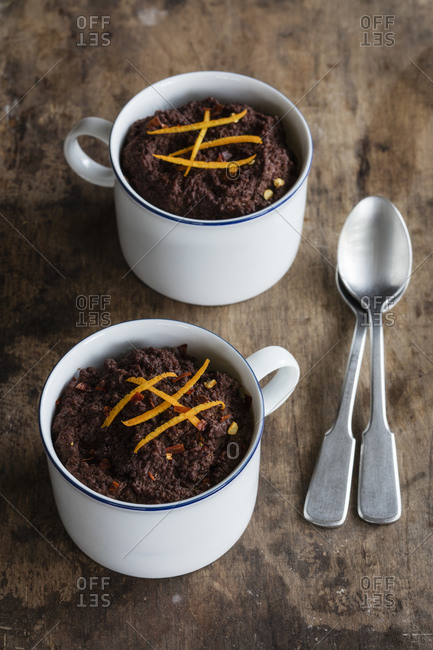 Mugs of gluten and lactose free chocolate puddings with canihua- chili and orange