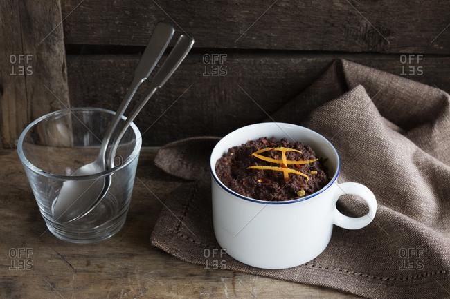 Mug of gluten and lactose free chocolate pudding with canihua- chili and orange