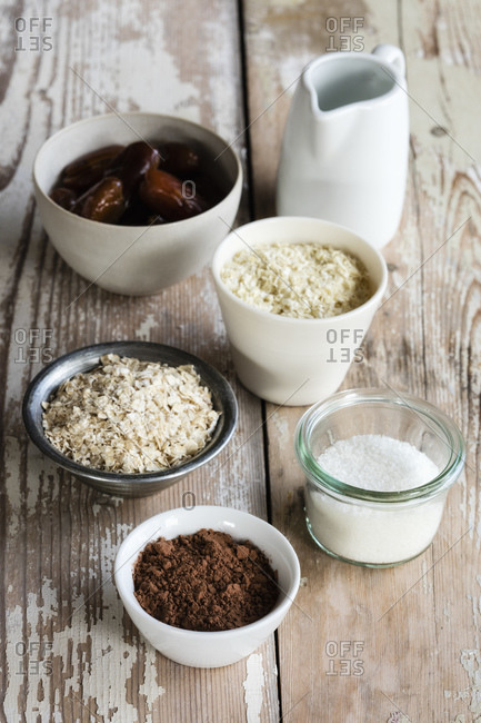 Ingredients for making protein balls (coconut oil- dates- millet flakes- oat flakes- grated coconut and cocoa powder)