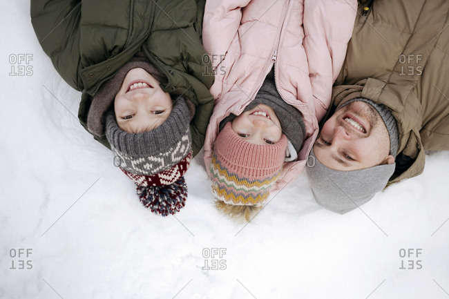 Family portrait of father and two children lying on snow