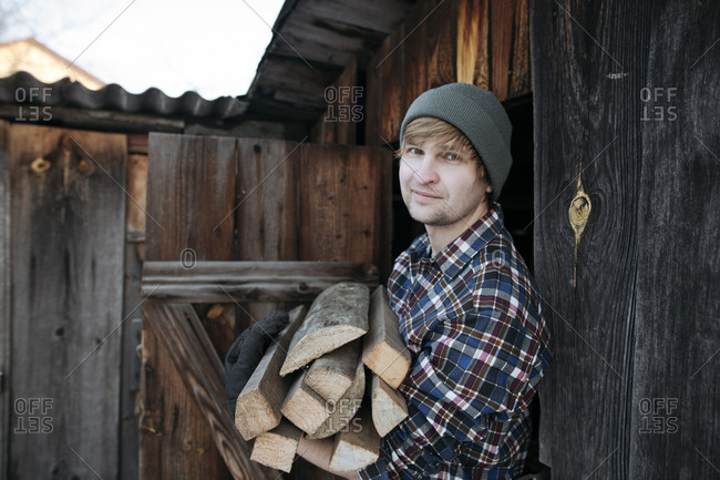 Portrait of man wearing wooly hat carying firewood