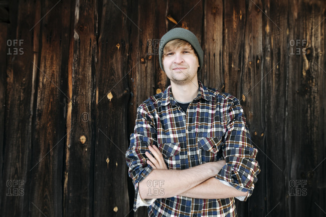 Portrait of confident man wearing wooly hat at wooden wall