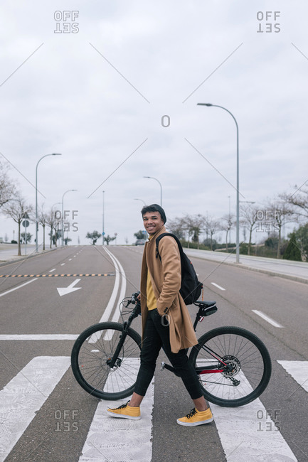 Young man with bicycle crossing a street in the city