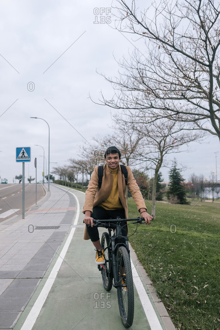 Portrait of smiling young man riding bicycle in the city