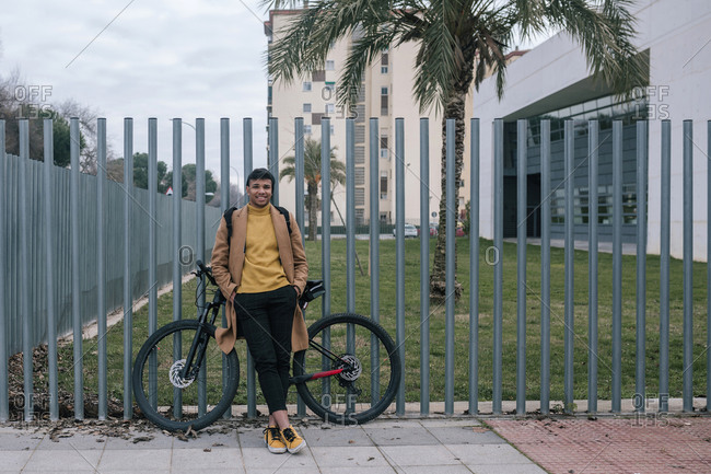 Portrait of smiling young man with bicycle in the city