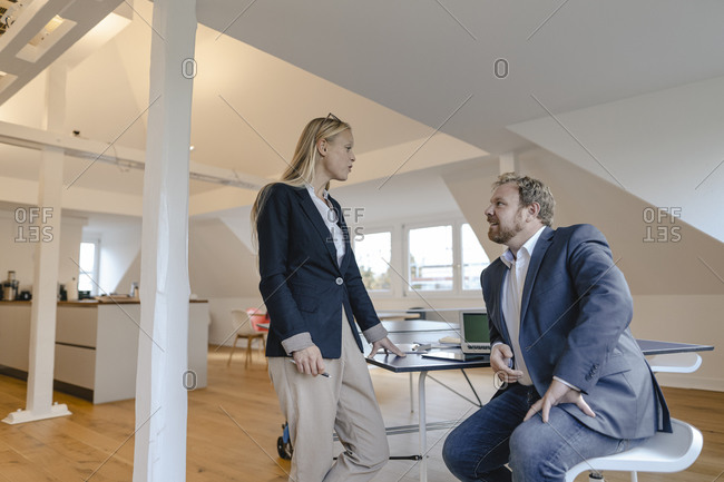 Businessman and businesswoman talking at table tennis table in office