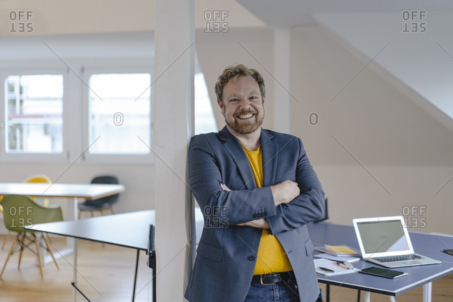 Portrait of a smiling businessman in office with table tennis table