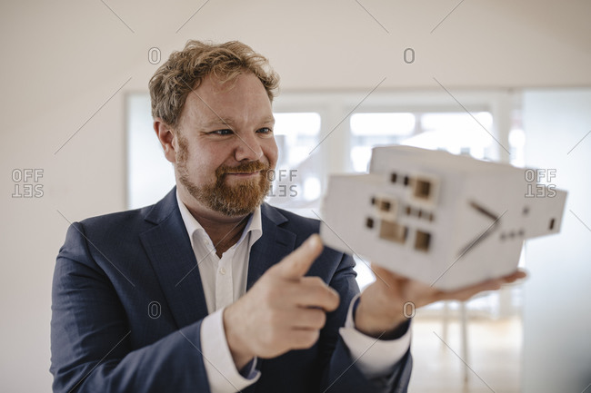 Businessman holding architectural model in office