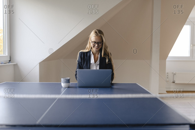 Young businesswoman using laptop on table tennis table in office