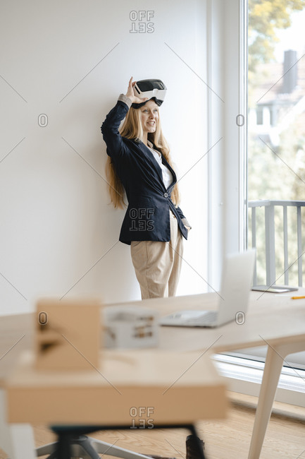 Smiling young businesswoman wearing VR glasses in office