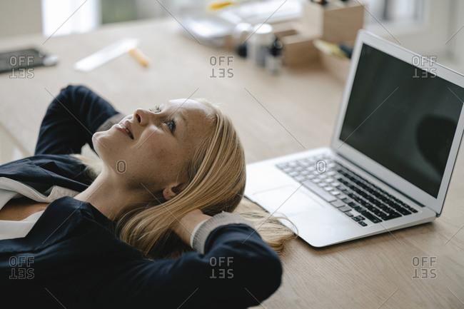 Young businesswoman having a break in office lying on desk