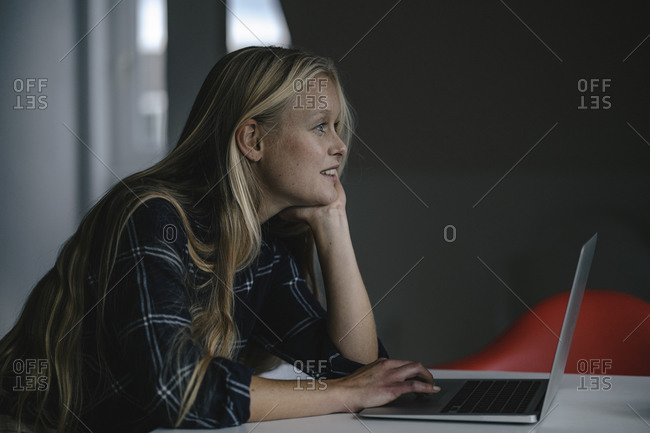 Casual young businesswoman using laptop in office