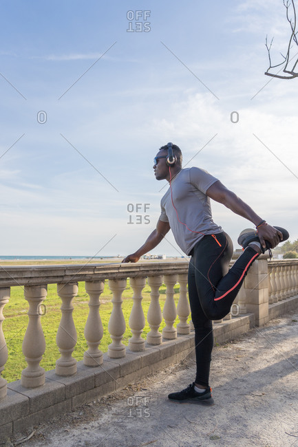 Muscular black man stretching on the promenade of Barcelona, Spain