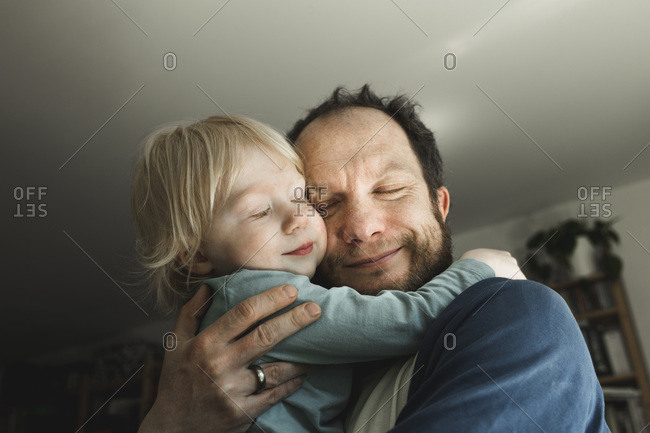 Affectionate father carrying little daughter at home