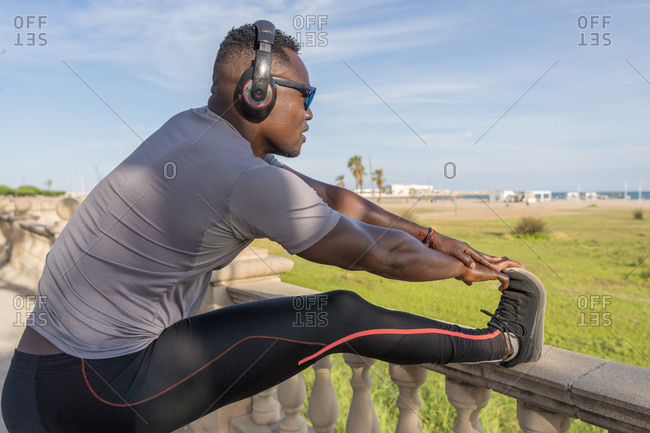 Close-up of a muscular black man stretching on the promenade of Barcelona, Spain