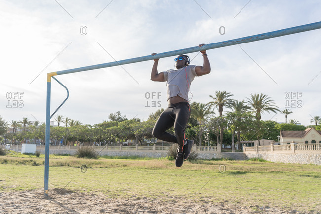 Muscular black man doing pull ups on a horizontal bar in the beach, working out