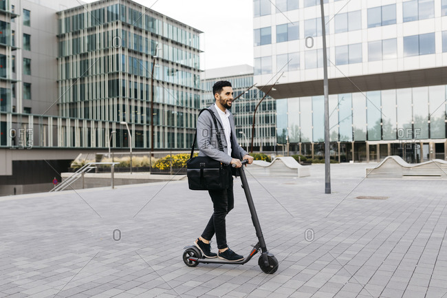 Casual young businessman riding electric scooter in the city