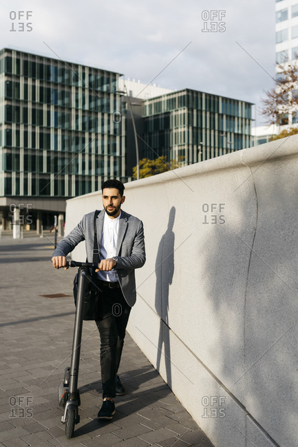 Casual young businessman pushing electric scooter in the city