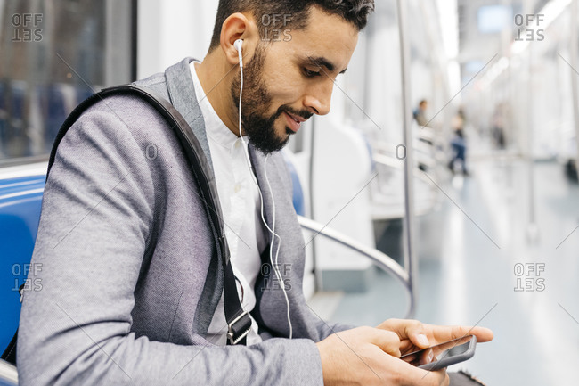 Young businessman with cell phone and earphones on the subway