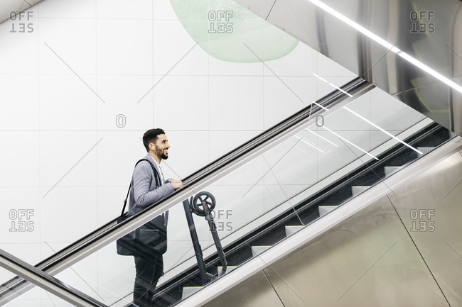 Smiling young businessman with electric scooter on escalator