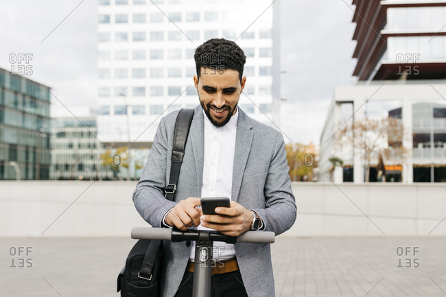 Casual young businessman with electric scooter using cell phone in the city